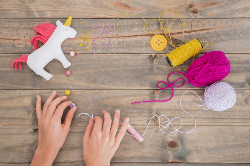 yellow-yarn-spool-wool-thread-and-beads-with-unicorn-on-wooden-desk (1) (1)